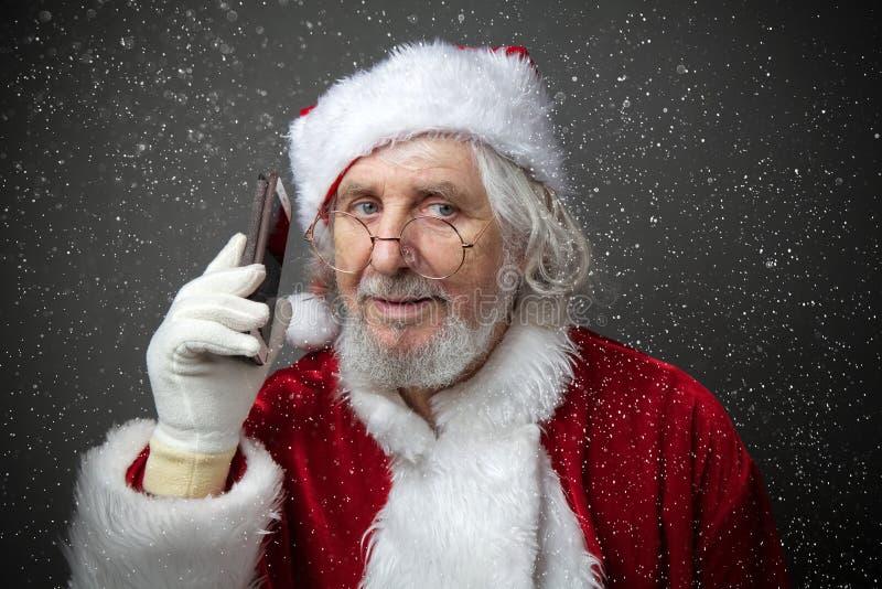 Santa Claus que usa o smartphone - chamando o telefone ou texting uma mensagem fotos de stock royalty free