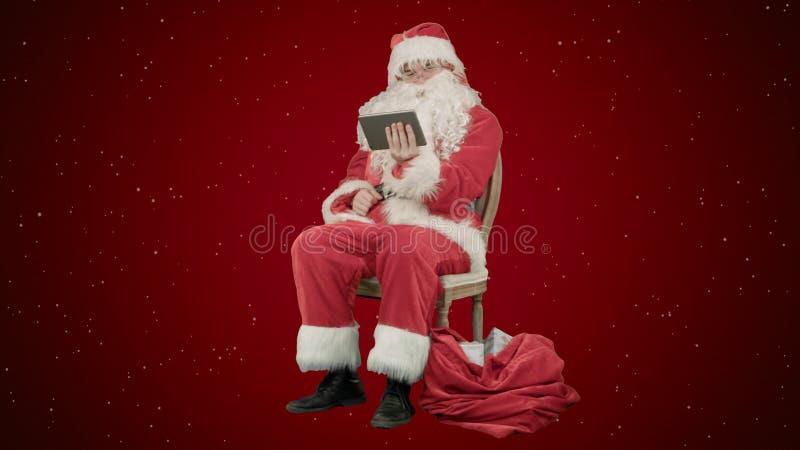 Santa Claus que usa o tablet pc para surfar o Internet e comunicar-se em meios sociais com as crianças no fundo vermelho com foto de stock royalty free