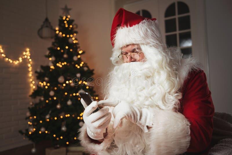 Santa Claus que usa um telefone, sentando-se em uma sala acolhedor fotos de stock