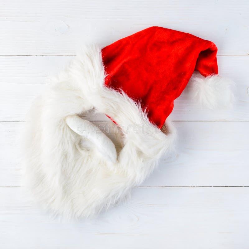 Santa Claus röd hatt och skägg på ljus träbakgrund glatt arkivbilder