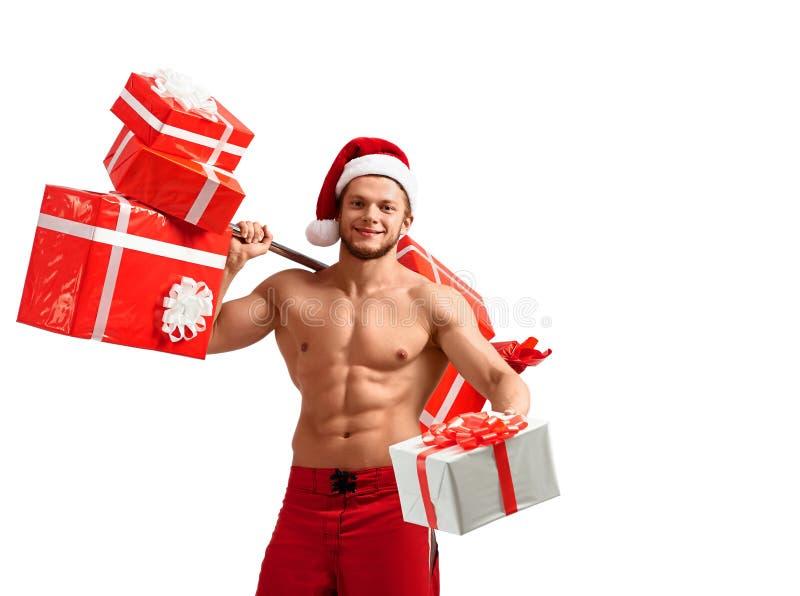 Santa Claus rasgada que guarda o barbell e que dá presentes fotografia de stock royalty free