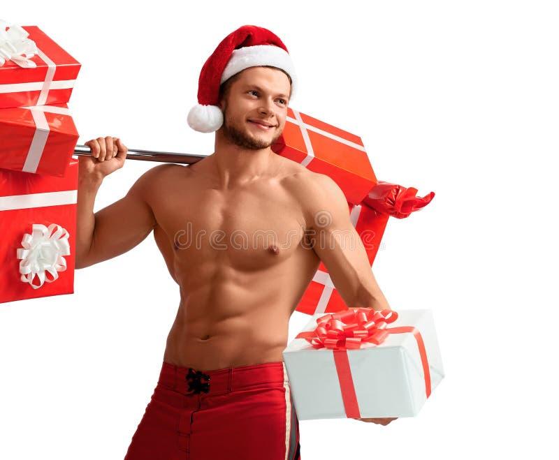 Santa Claus rasgada que guarda o barbell e que dá presentes imagem de stock royalty free