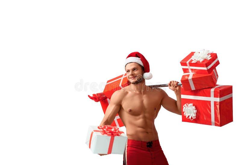 Santa Claus rasgada que guarda o barbell e que dá presentes foto de stock