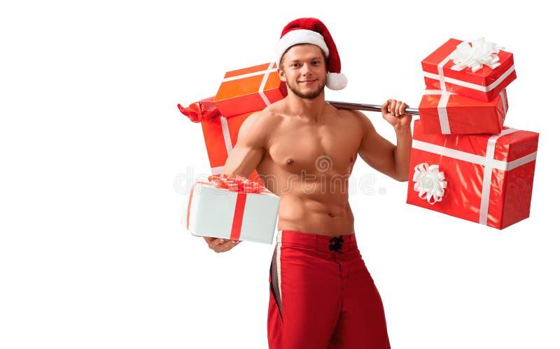 Santa Claus rasgada que guarda o barbell e que dá presentes imagem de stock