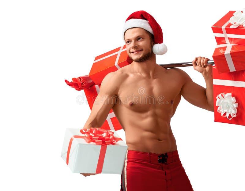 Santa Claus rasgada que guarda o barbell e que dá presentes imagens de stock