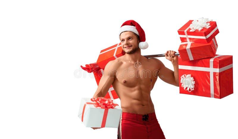 Santa Claus rasgada que guarda o barbell e que dá presentes fotos de stock