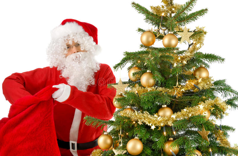 Santa Claus reaching into his bag. Santa Claus beside a Christmas tree with gold ornaments, looking into the camera and reaching into his bag of gifts stock photography