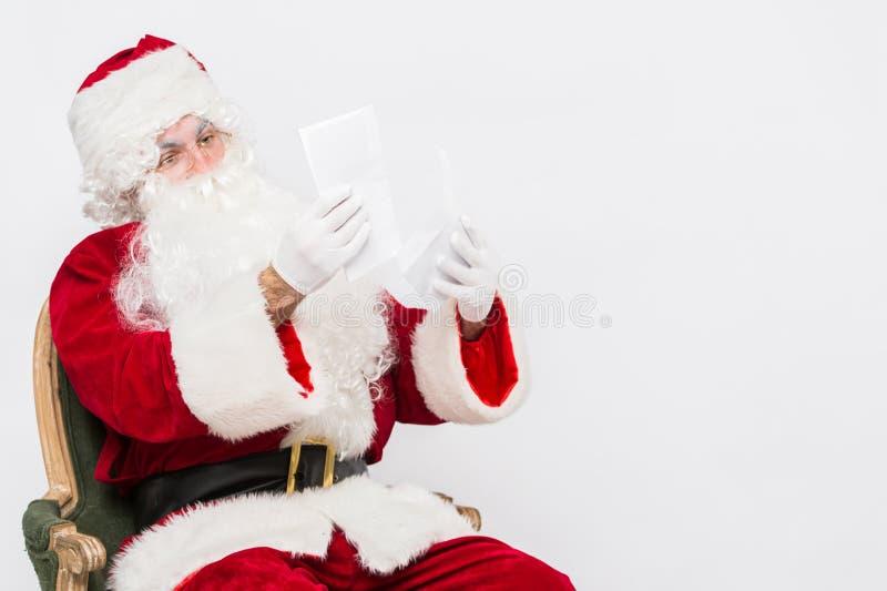 Santa Claus Reading Letter a isolé au-dessus du baclground blanc image libre de droits