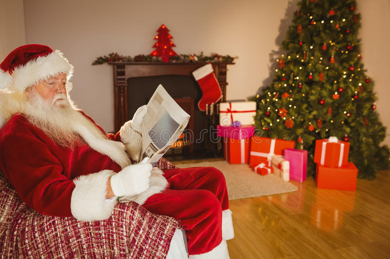Santa claus reading newspaper on the couch stock photo