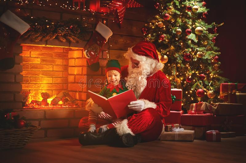 Santa claus reads a book to a little elf by Christmas tree stock photography