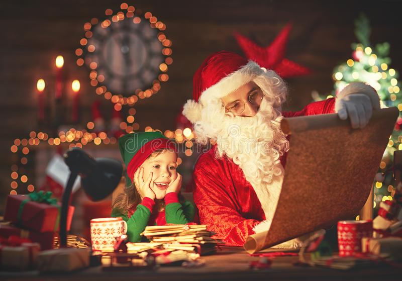 Santa claus reads list of good children to little elf by Christmas tree. Santa claus reads list of good children to little elf by fireplace and Christmas tree royalty free stock image