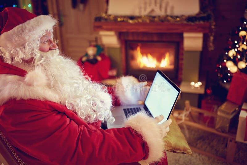 Santa Claus real que usa a nova tecnologia para uma comunicação com o qui fotos de stock