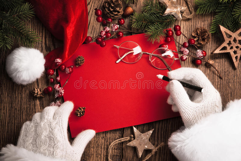 Santa Claus with red card. Santa Claus with gifts and red card on wooden table royalty free stock photos
