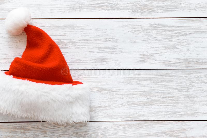 Santa claus red hat on white wooden background, merry marry Christmas card with xmas holiday cap, copy space, top view. Santa claus red hat with white fluffy fur royalty free stock photos