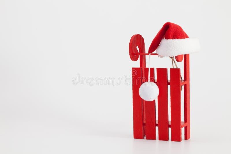 Santa Claus Red Wodden Sleigh met Santa Cap op wit t wordt geïsoleerd dat stock foto