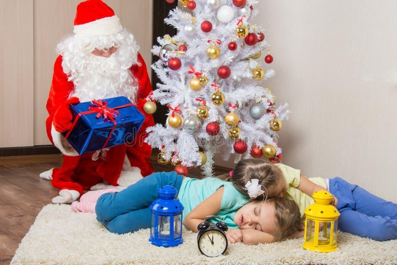 Santa Claus in regali di EVE dei nuovi anni presenta ed esaminato l'addormentato caduto davanti ai bambini dell'albero di Natale  immagini stock libere da diritti