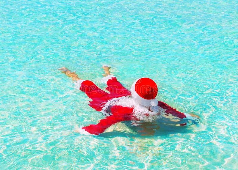Santa Claus relaja la natación en agua del océano, la Navidad c que viaja foto de archivo libre de regalías