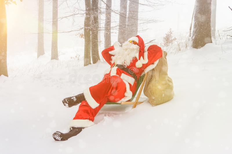 Santa Claus relaxing in a lounger in the woods royalty free stock photos