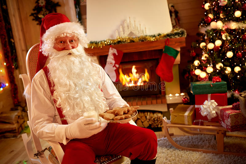 Santa Claus resting in warm room and eating traditional Christmas cookie royalty free stock photography