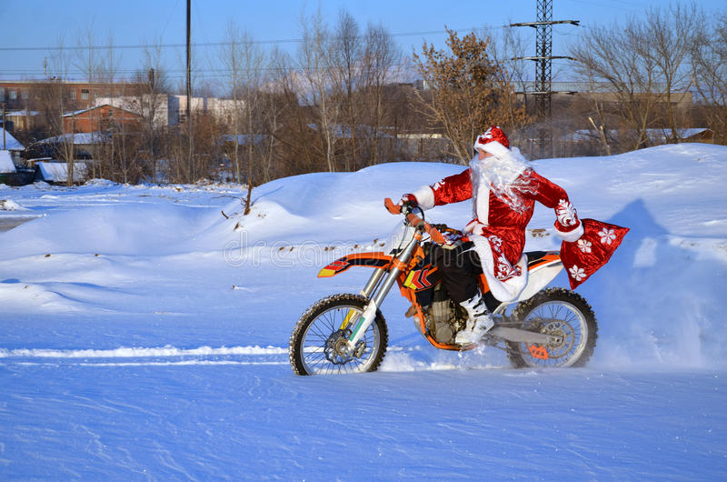 Santa Claus riding on a bike MX through deep snow. Santa Claus riding on a motocross bike in a red coat through the snow holds in a hand bag with gifts royalty free stock image