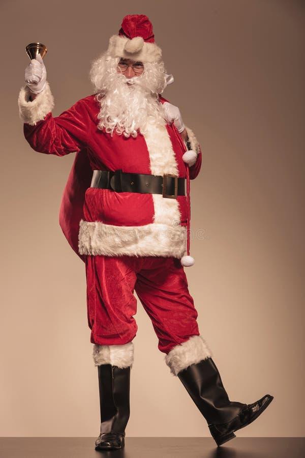 Santa Claus ringing a bell and holding a big bag stock photos