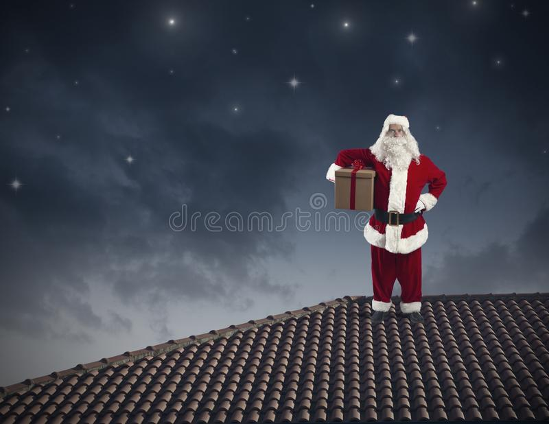 Santa Claus on a roof. Santa Claus with a big present on a roof royalty free stock photo
