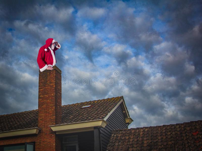 Merry Christmas and happy holidays! Santa Claus sitting in a chi stock photography