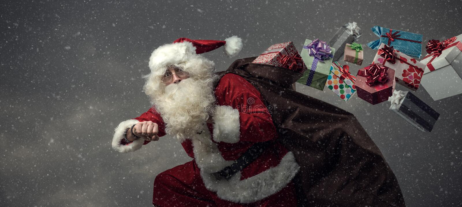 Santa Claus running and delivering gifts royalty free stock image