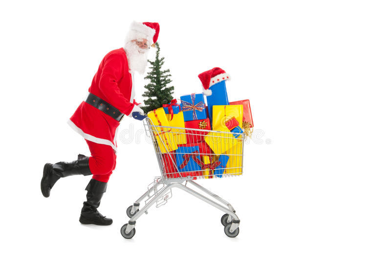 Santa Claus running with shopping cart. Full luxury presents and tree stock photo