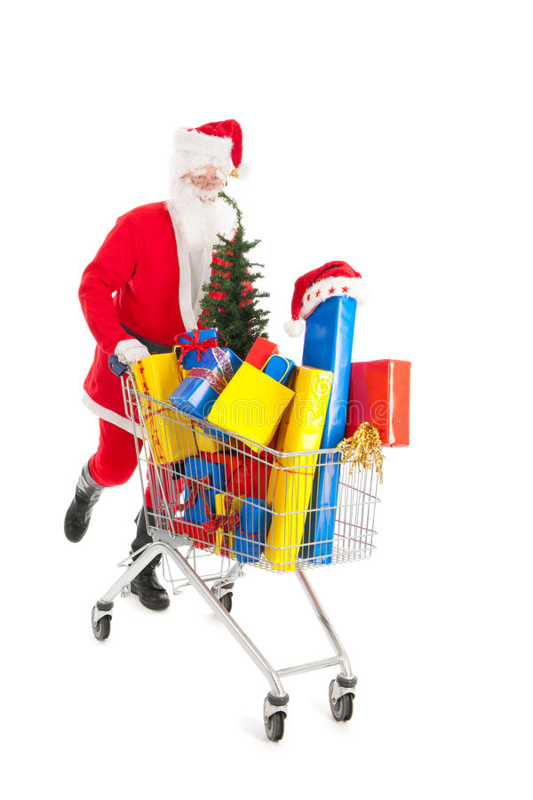 Santa Claus running with shopping cart. Full luxury presents and tree royalty free stock photo