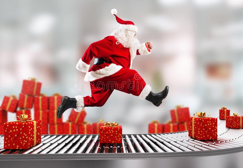Santa Claus runs on the conveyor belt to arrange deliveries at Christmas time royalty free stock images