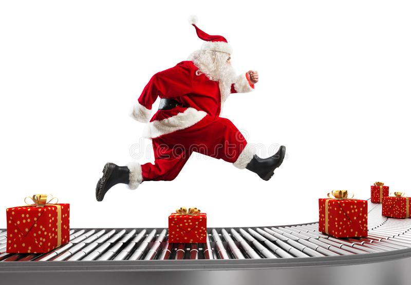 Santa Claus runs on the conveyor belt to arrange deliveries at Christmas time. Christmas is coming. Santa Claus struggling with deliveries stock photo