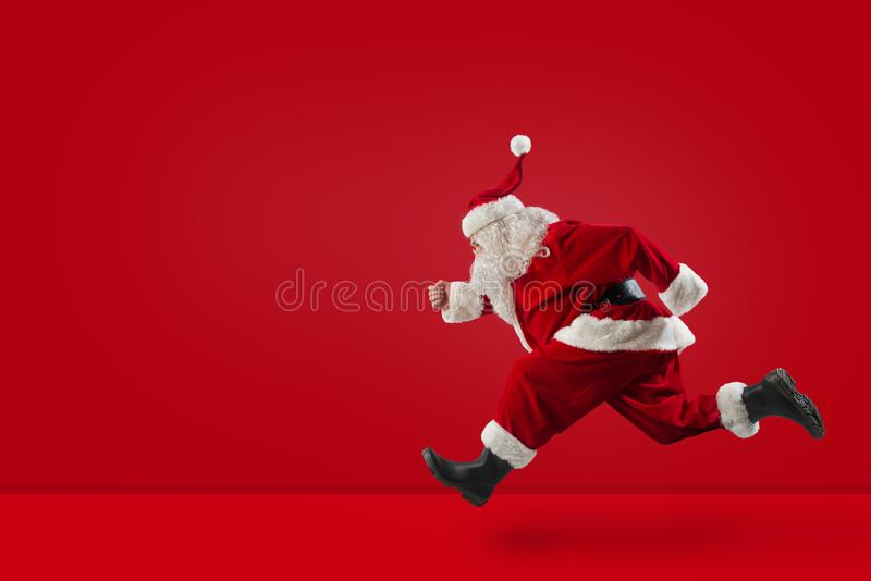 Santa Claus runs fast on red background. Santa Claus runs fast to prepare Christmas presents on red background royalty free stock images