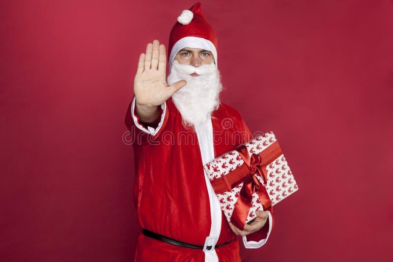 Santa Claus rymmer en gåva och säger stoppet royaltyfri fotografi