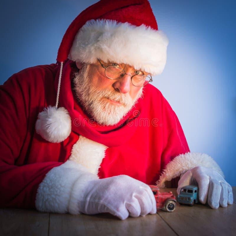 Santa Claus sérieuse joue avec des voitures de jouets de vintage à la maison photographie stock