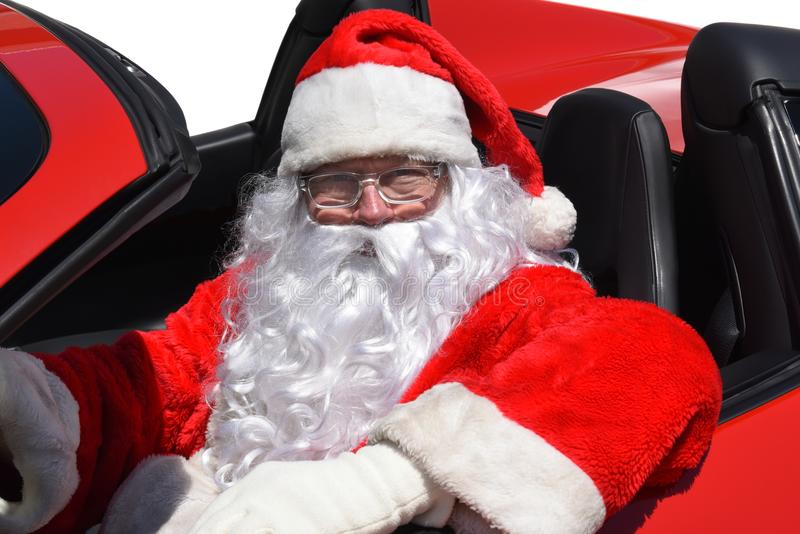 Santa Claus s'asseyant dans sa voiture de sport rouge toute neuve images stock
