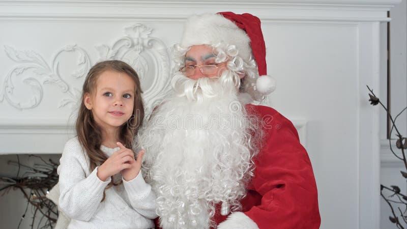 Santa Claus s'asseyant dans une chaise avec une petite fille rêvant de ses cadeaux de Noël photos stock