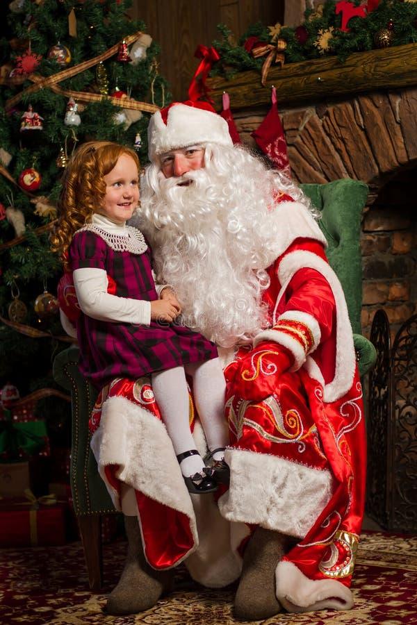 Santa Claus s'asseyant dans une chaise avec une petite fille photos libres de droits