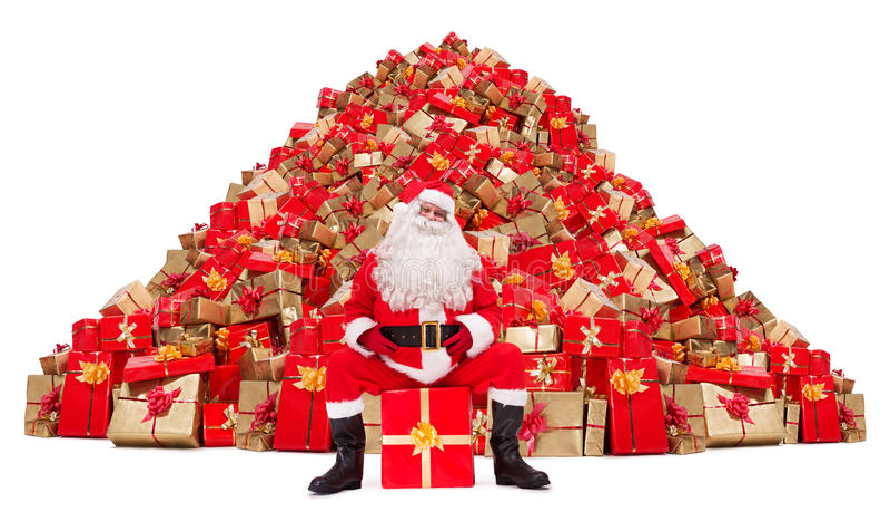 Santa Claus s'asseyant devant une pile des cadeaux de Noël photographie stock libre de droits