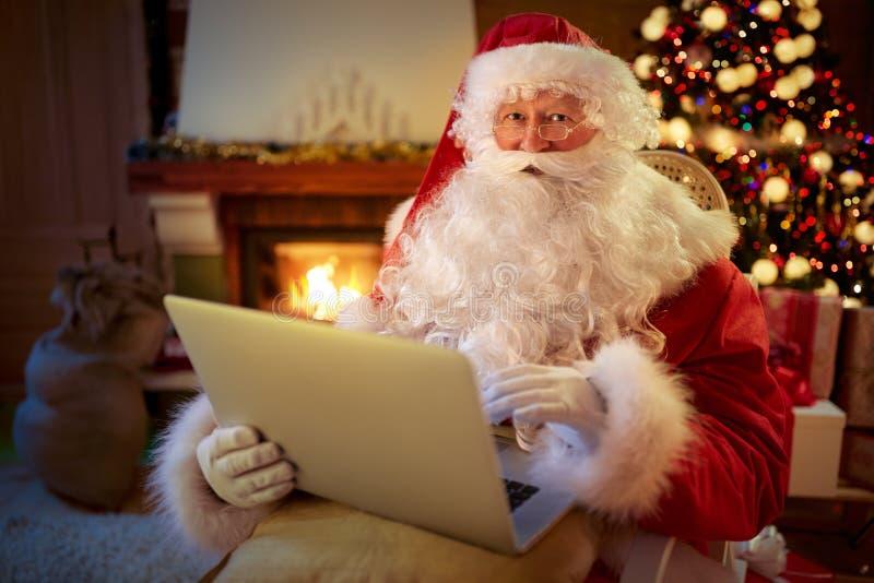Santa Claus s'asseyant par la cheminée avec l'ordinateur portable images libres de droits
