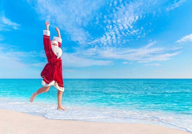 Santa Claus salta na praia do mar no céu, conceito do Natal fotos de stock