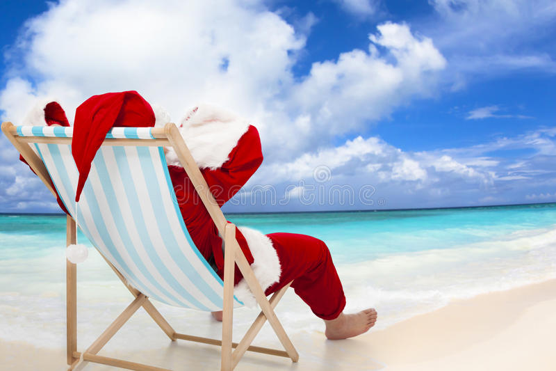 Santa Claus sammanträde på strandstolar Julferiebegrepp fotografering för bildbyråer