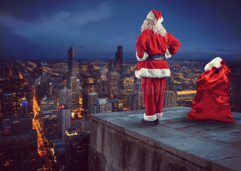 Santa Claus schaut unten auf der Stadt, die wartet, um die Geschenke zu liefern lizenzfreies stockfoto
