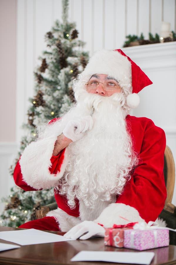 Santa Claus schrijft de brief en het richten met zijn vinger stock foto