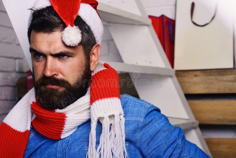 Santa Claus se coloca cerca de la escalera y de los estantes blancos en el fondo blanco del ladrillo Días de fiesta y concepto de imagen de archivo libre de regalías