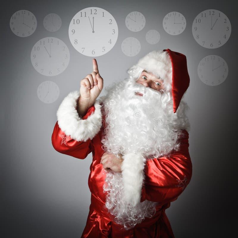 Santa Claus se dirige à l'horloge photos stock