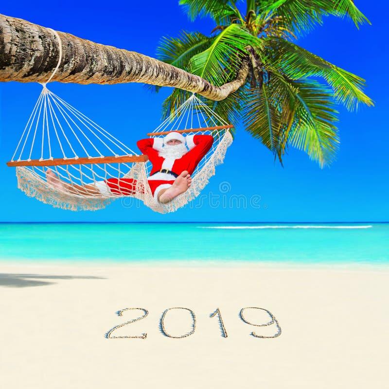 Santa Claus se relaja en hamaca debajo de la palmera en la playa tropical de la isla con Feliz Año Nuevo del subtítulo 2019 manus fotografía de archivo