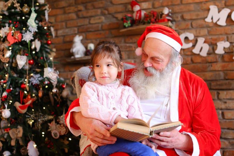 Santa Claus se sienta en la butaca y lee el libro con los cuentos de hadas FO foto de archivo