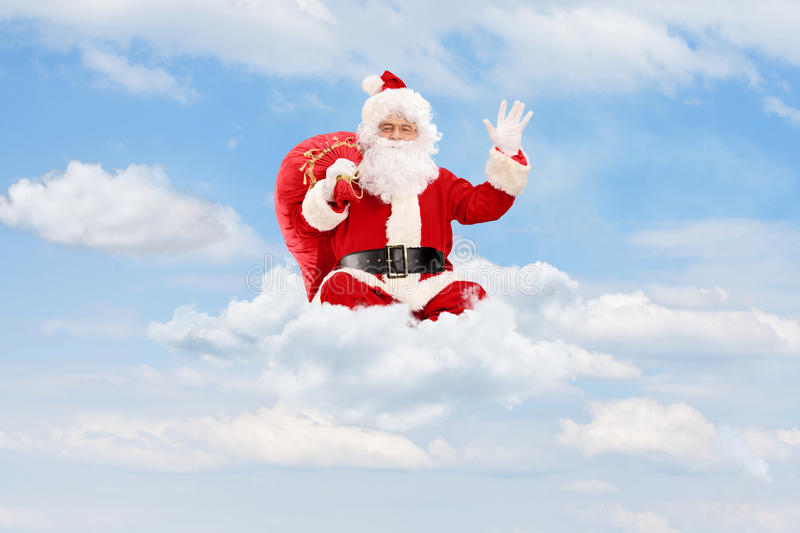 Santa Claus seated on clouds holding a bag and waving royalty free stock photos