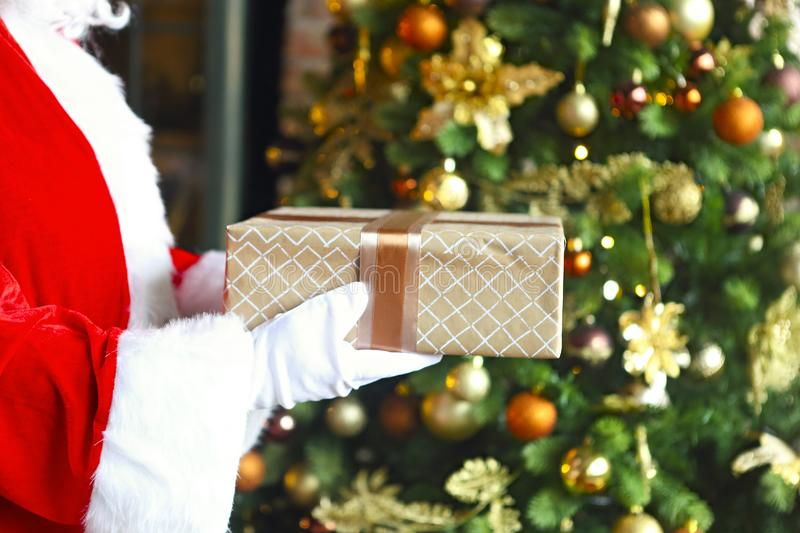 Santa Claus secretly putting gift box by the Christmas tree royalty free stock image